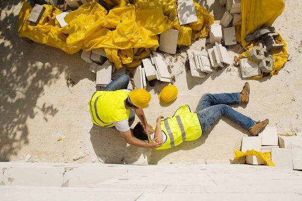 Construction worker helping an injuredc construction worker